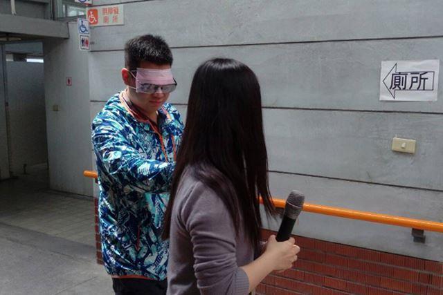 受訓人員遮住雙眼,體驗視障者無導盲杖,由他人協助行進之情形